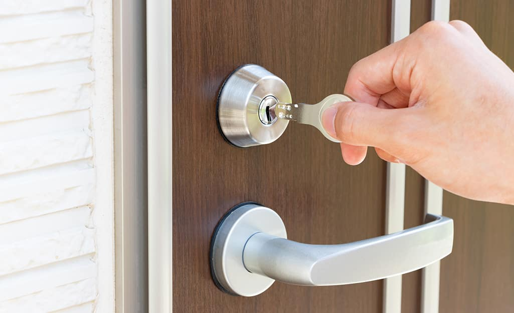 A hand inserting a key into a front door lock.
