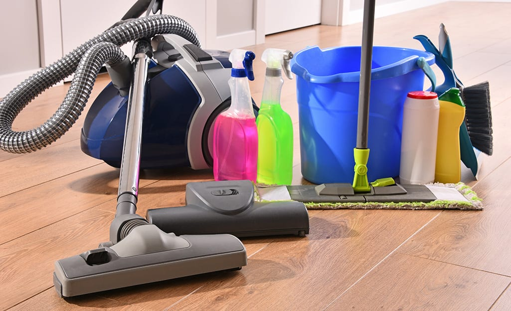 An assortment of cleaning supplies on a wood floor.