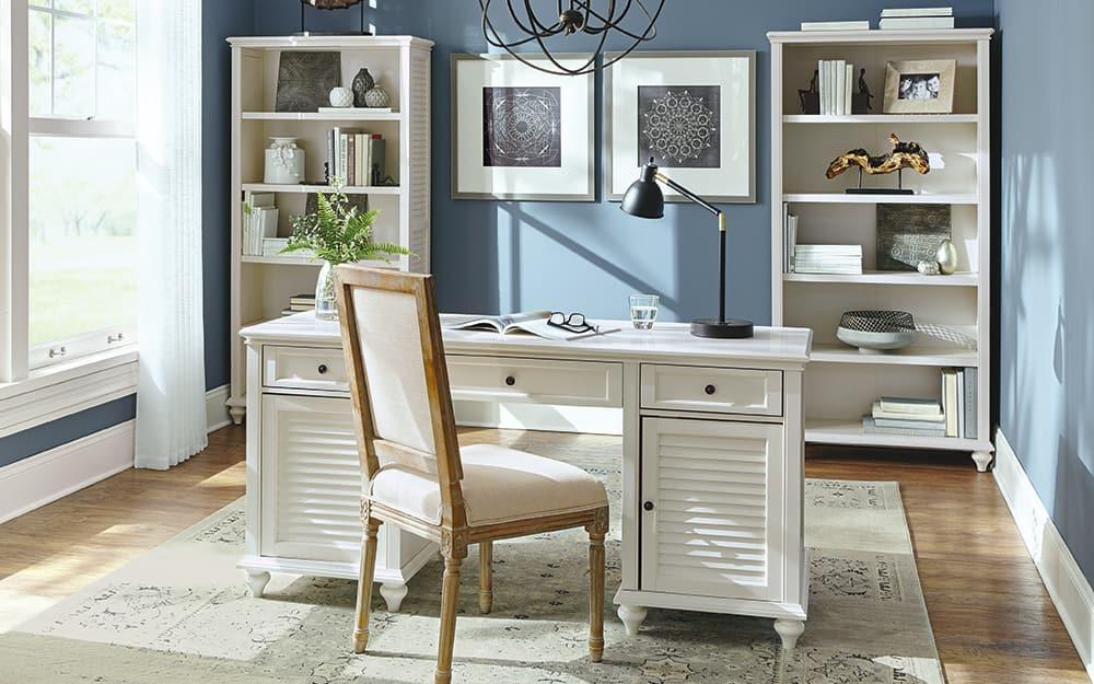 Home office with desk, chair and bookshelves.