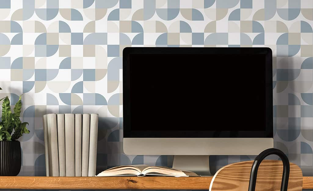Wallpaper in a modern blue, gray and white design behind a computer monitor.