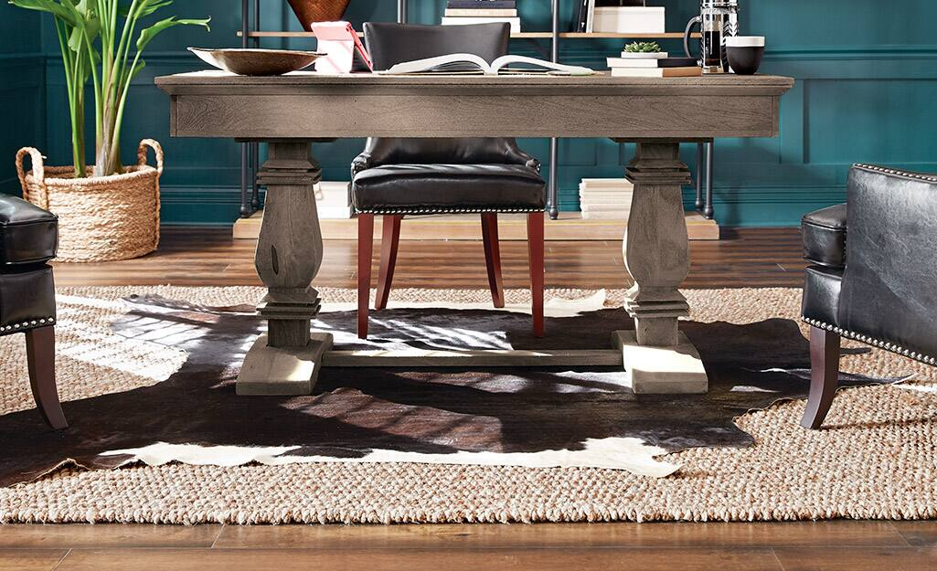 Layered rugs under a pedestal desk.