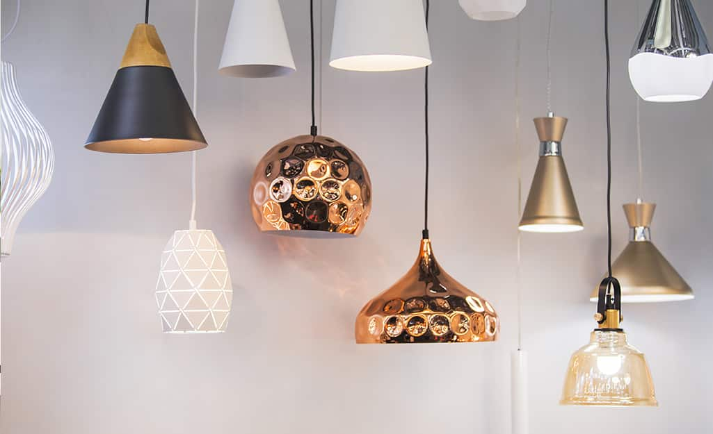 Several copper, white and silver metal pendant lights hanging against a white wall.