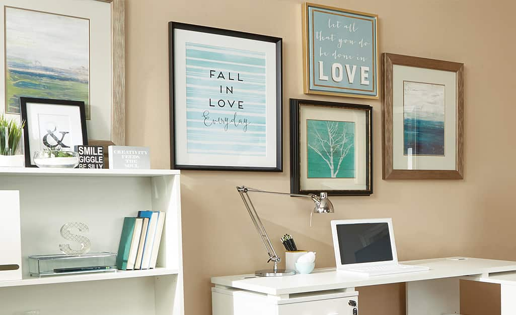 Wall art hanging above a petite desk in a home office.