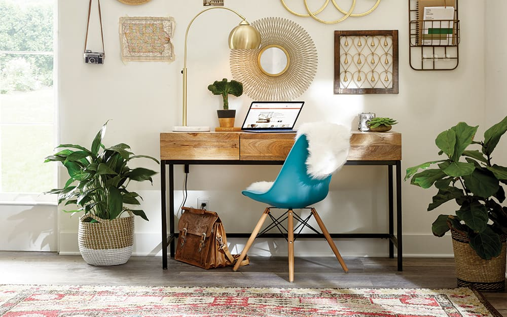 Home office with desk, chair, plants and wall art.