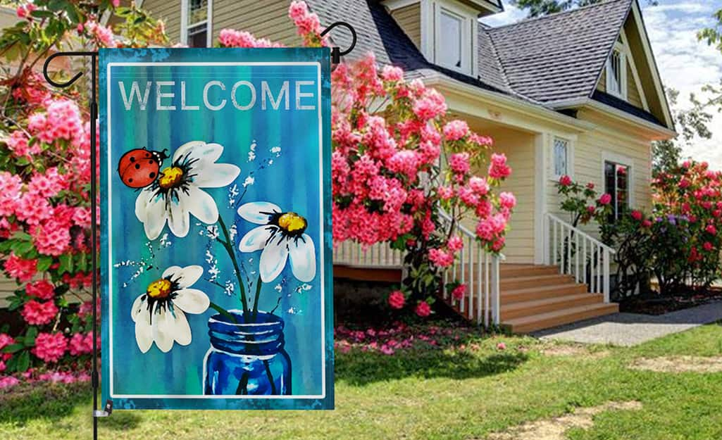 """A garden flag showing the word """"welcome"""" and a jar filled with daises hanging outside a home."""