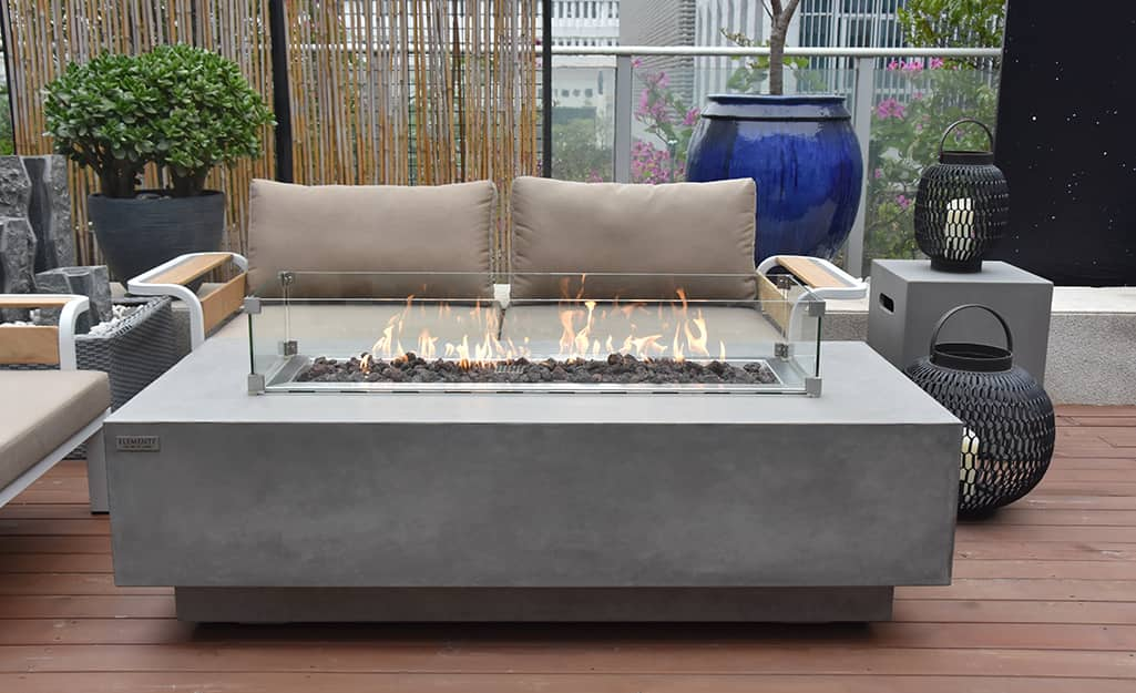 A contemporary fire pit with an outdoor love seat on a deck.