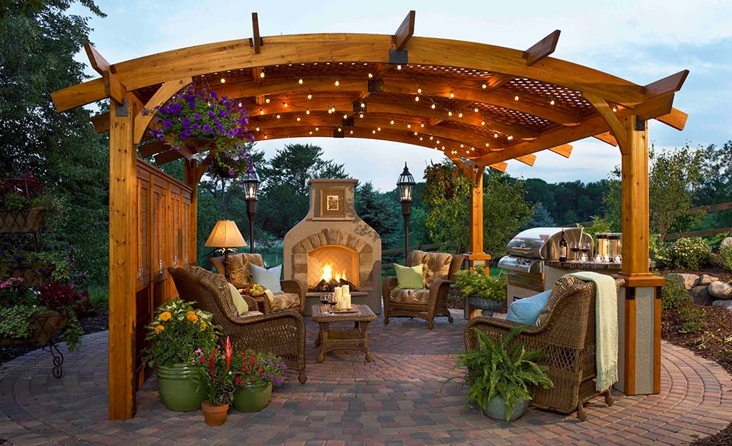 An arbor strung with white lights over patio chairs near an outdoor fireplace.