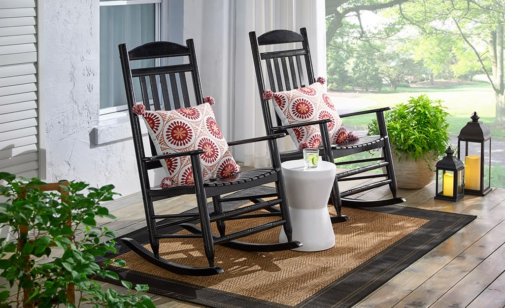 Two black rockers with colorful pillows and a garden stool beside plants on a front porch.