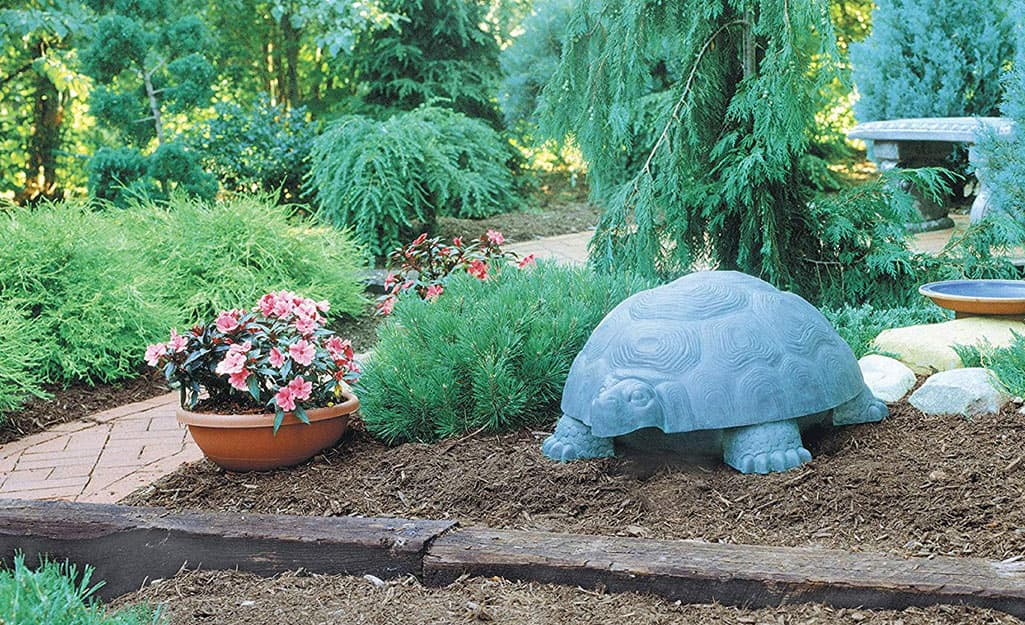 A faux turtle beside some foliage plants and flowers in a garden bed.
