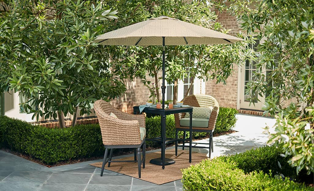A market umbrella over an outdoor table and two chairs on a patio.