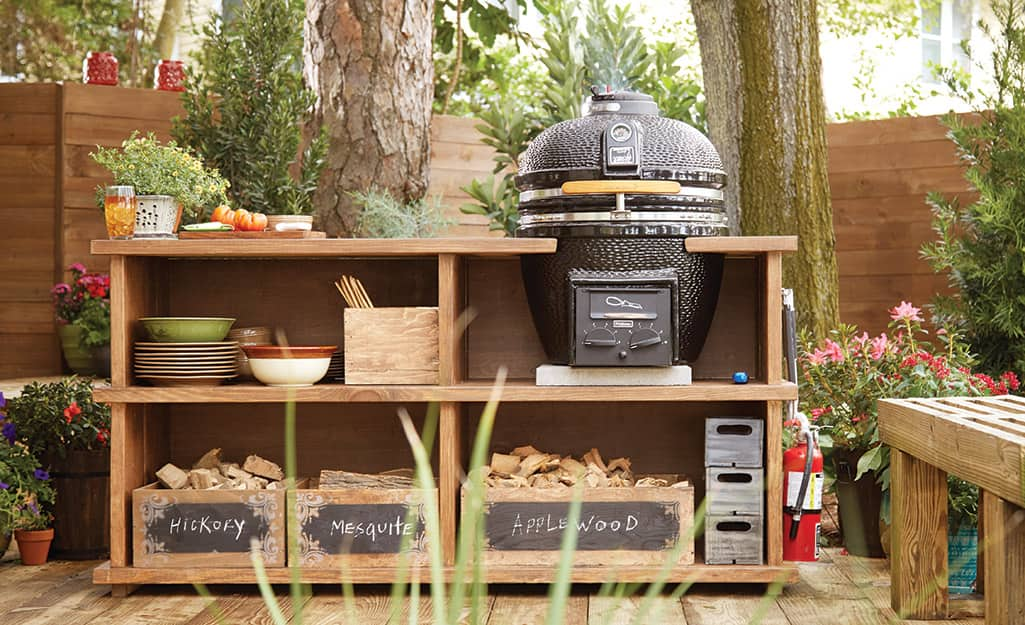 A grill and wood grilling station in an outdoor living space.