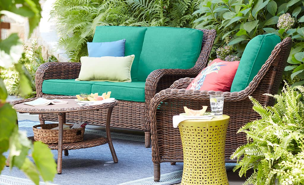 A brown outdoor loveseat and chair with green cushions beside a small table and garden stool in an outdoor space.