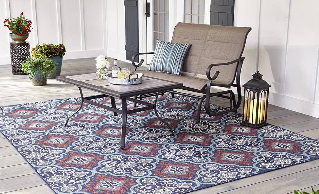 An outdoor love seat, coffee table and lantern on a patterned outdoor rug.