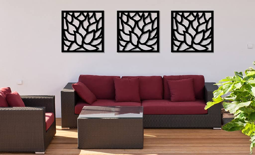 Three pieces of outdoor wall art hung on a white wall over a sofa.