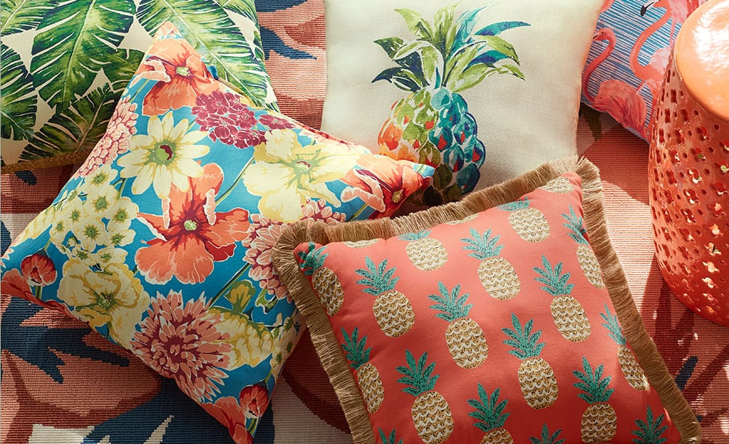 Several colorful outdoor pillows in an outdoor living space.