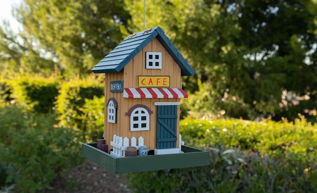 A birdhouse painted to look like a cafe sitting outdoors.