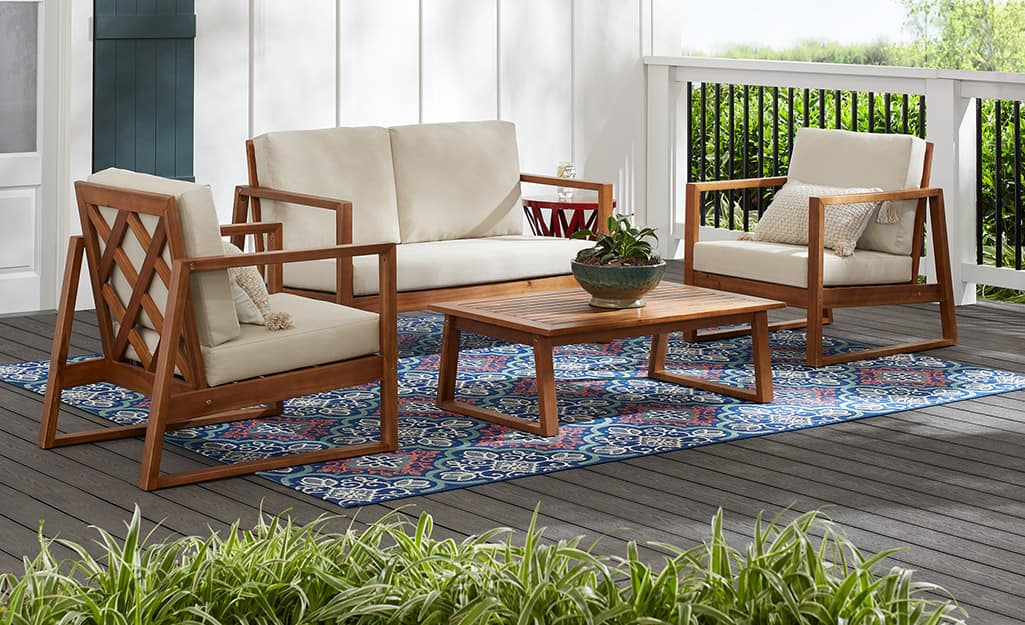 A patio love seat and chairs with ivory cushions and a coffee table on a colorful rug.