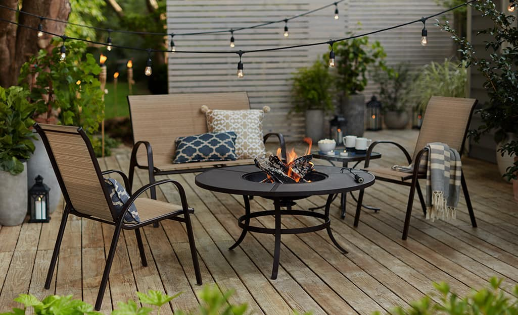 Globe lights strung over a black and tan love seat and chairs and a glowing fire pit.