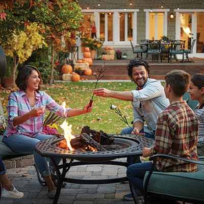 Group roasting marshmallows over an outdoor fire pit