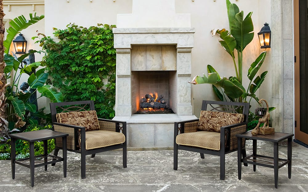 An outdoor fireplace made of light-colored stone on a patio.
