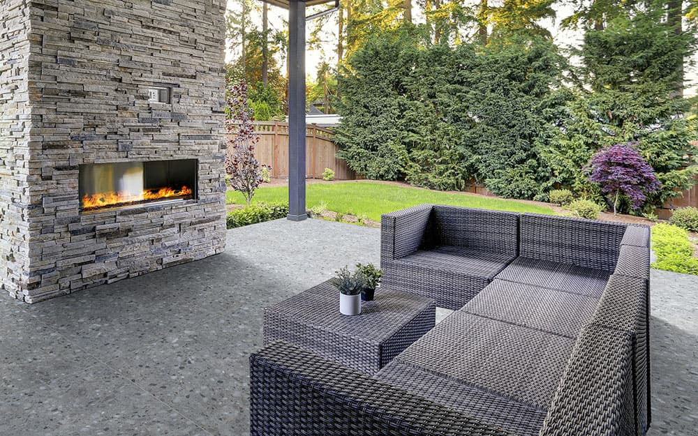 A modern outdoor fireplace has a gas fire and seating on a fireplace,