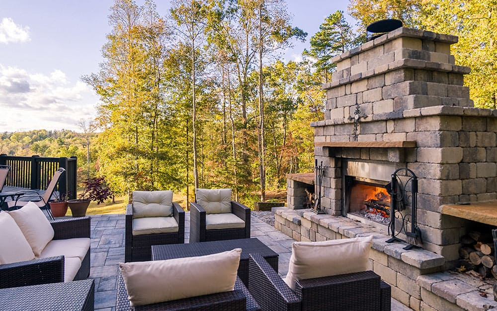 A large outdoor fireplace made of stone blocks has storage for firewood and seating.
