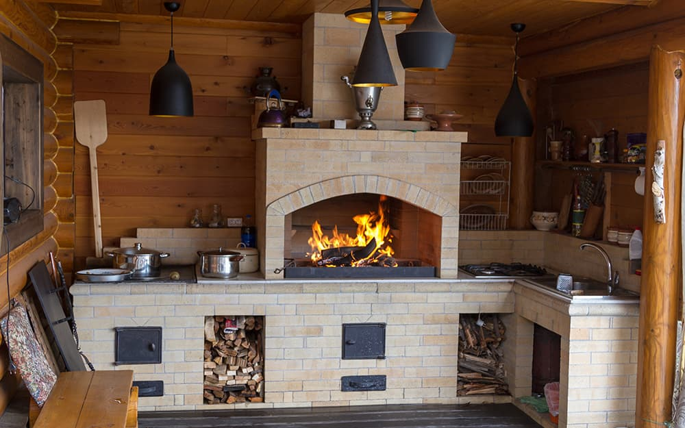 A brick fireplace with a wood fire and kitchen amenities built in.