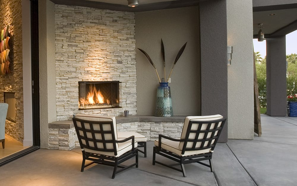 An outdoor fireplace has a modern feel on a covered patio.