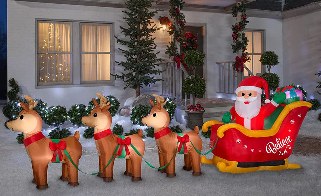 An inflatable Santa in his sleigh with reindeer in front of a home.