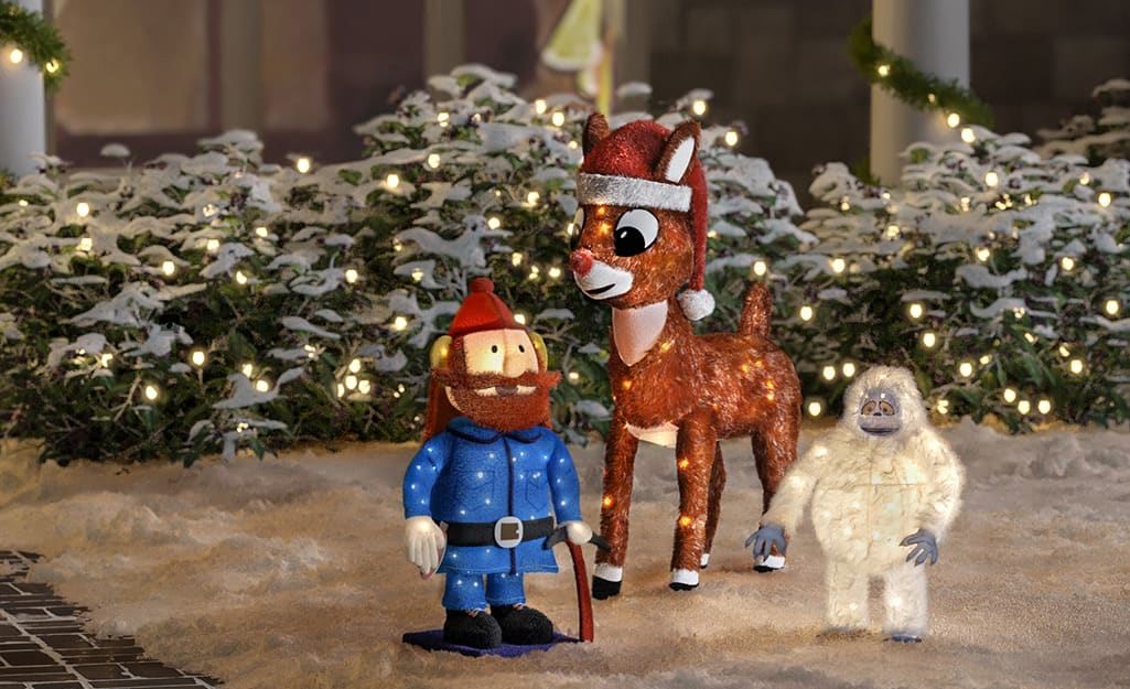 Characters from animated Christmas films are outdoor holiday decorations in front of a home.