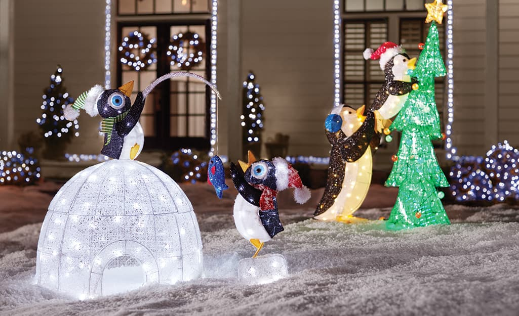 Whimsical animals building an igloo and decorating a Christmas tree.