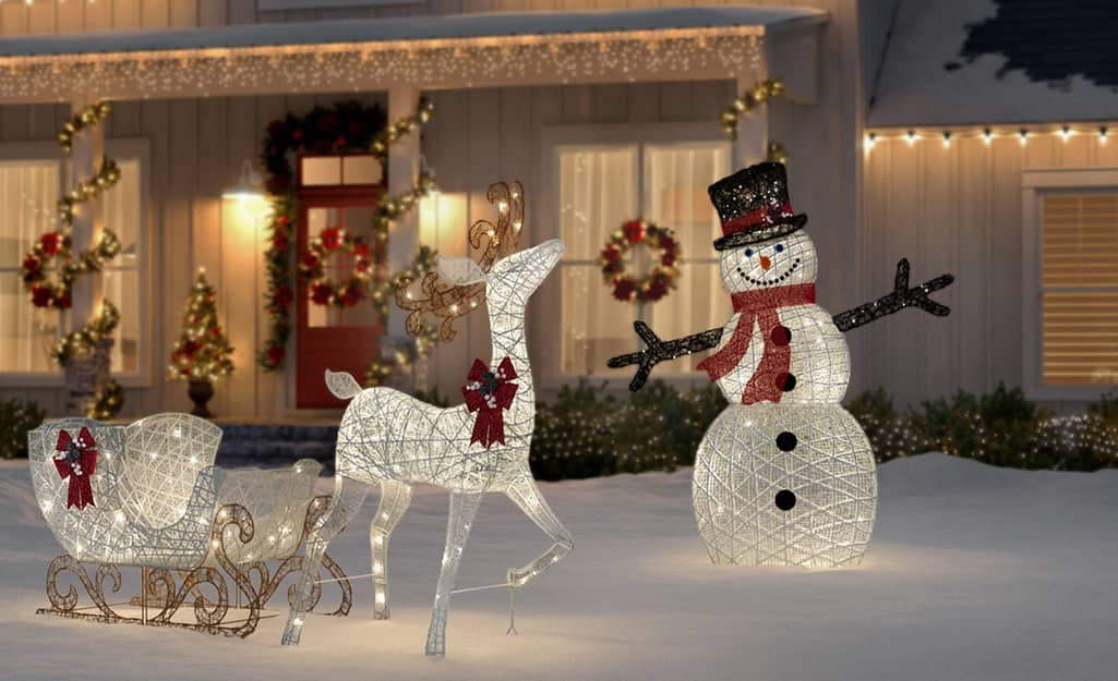 A pre-lit snowman, sleigh and reindeer are outdoor holiday decorations in front of a home.