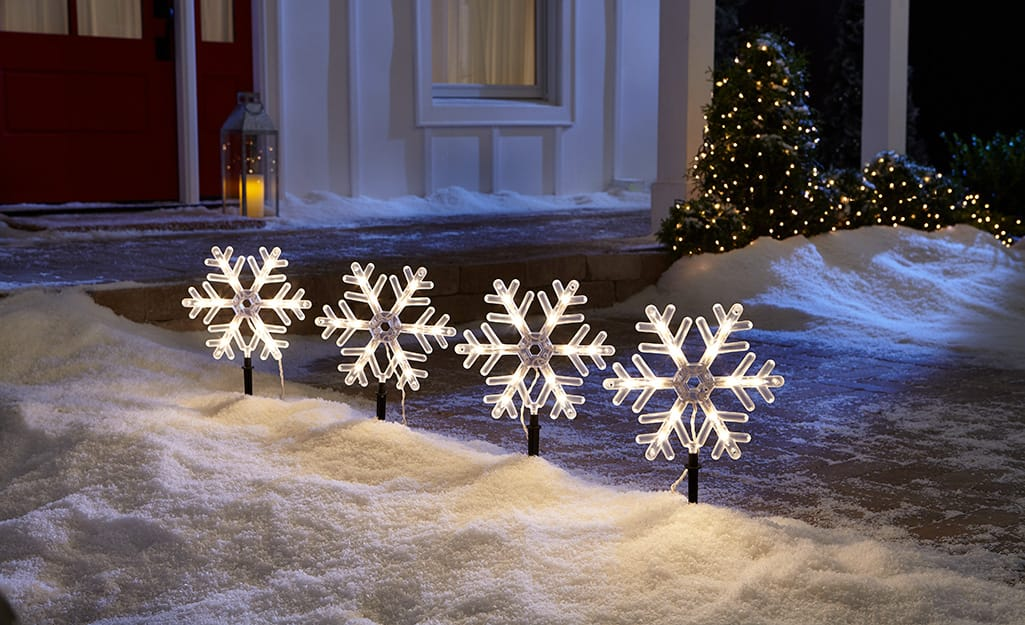 Illuminated snowflake decorations line a walkway in front of a home.