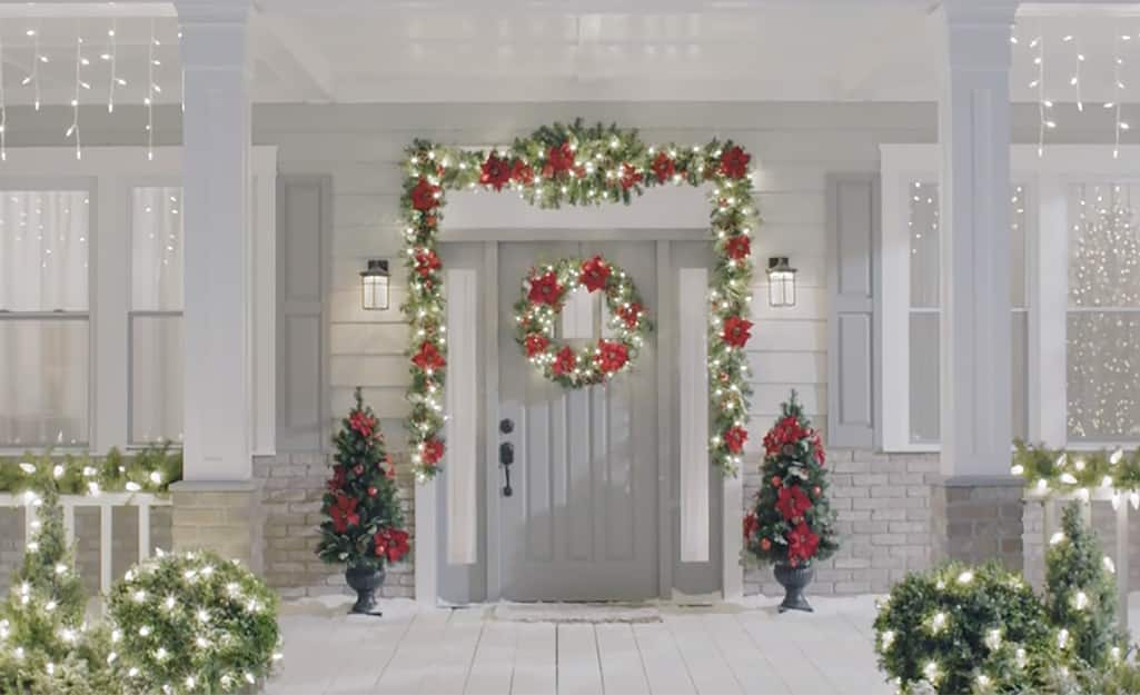 White lights decorate a wreath, garland and bushes at a home's entryway.