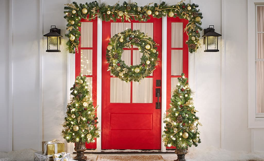 A home's entryway is decorated with porch Christmas trees, garland and a wreath.