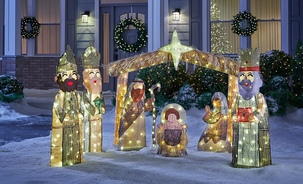 A lighted Nativity scene decorates a home's front yard.