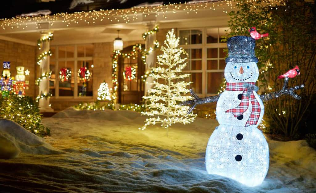 A home is brightly decorated with string lights on trees and roofline and a lighted snowman in the yard.