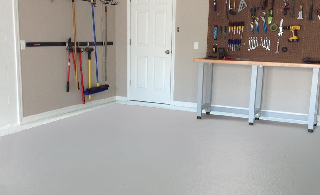 A garage workspace that has an off-white painted concrete floor.