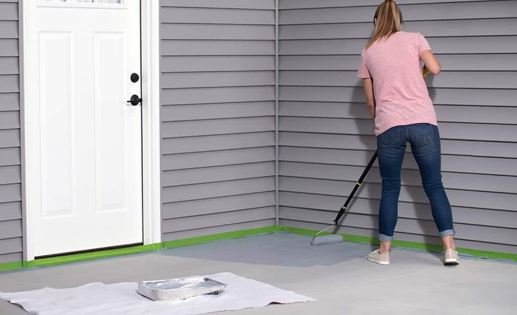 A woman uses a paint roller to paint a concrete patio.