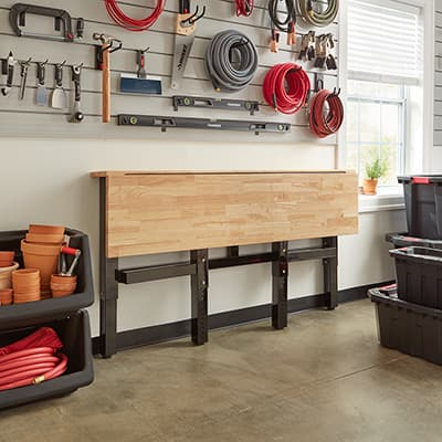 A garage workspace that has a concrete floor stained the color of sandstone.