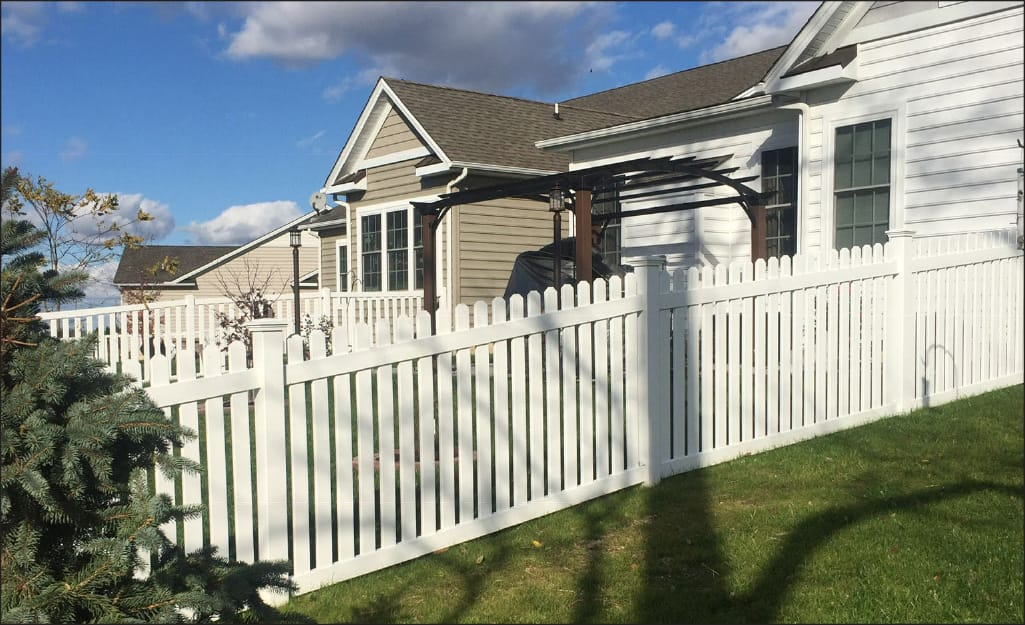 White picket fencing stands at the edge of a yard.
