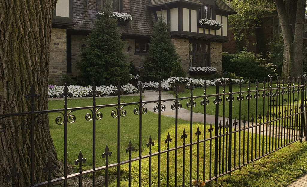 An ornamental metal fence stands in front of a Tudor-style home
