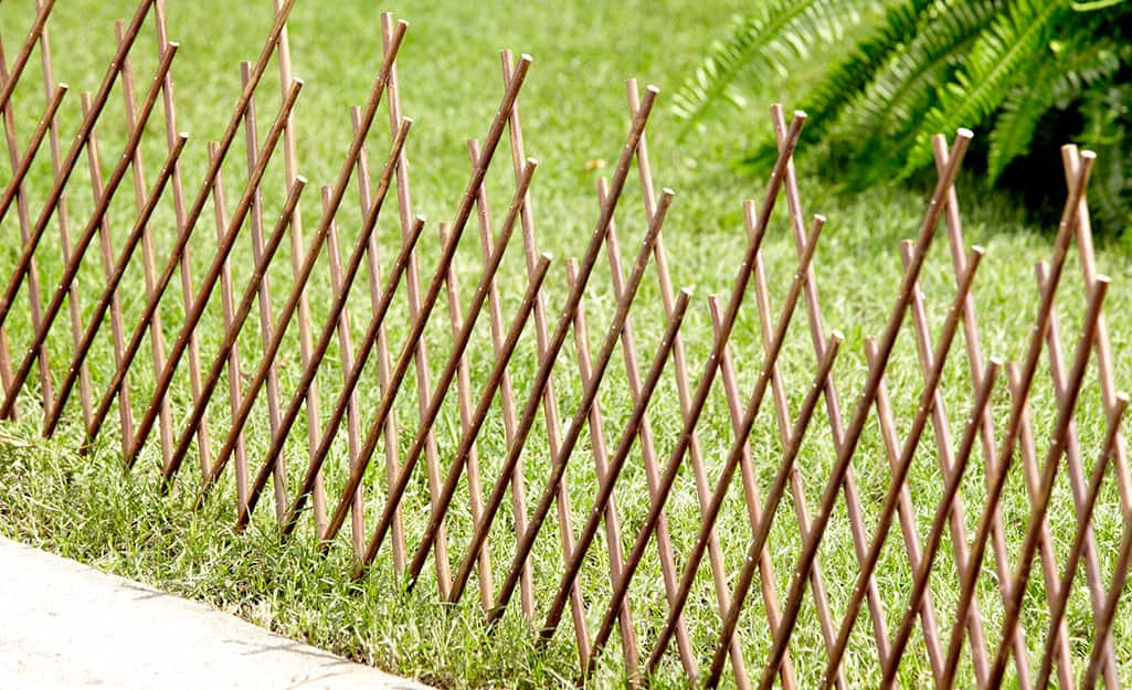 An expandable privacy fence stretches along a lawn