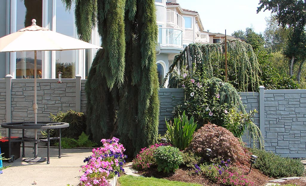 A gray privacy fence that looks like stone divides two yards