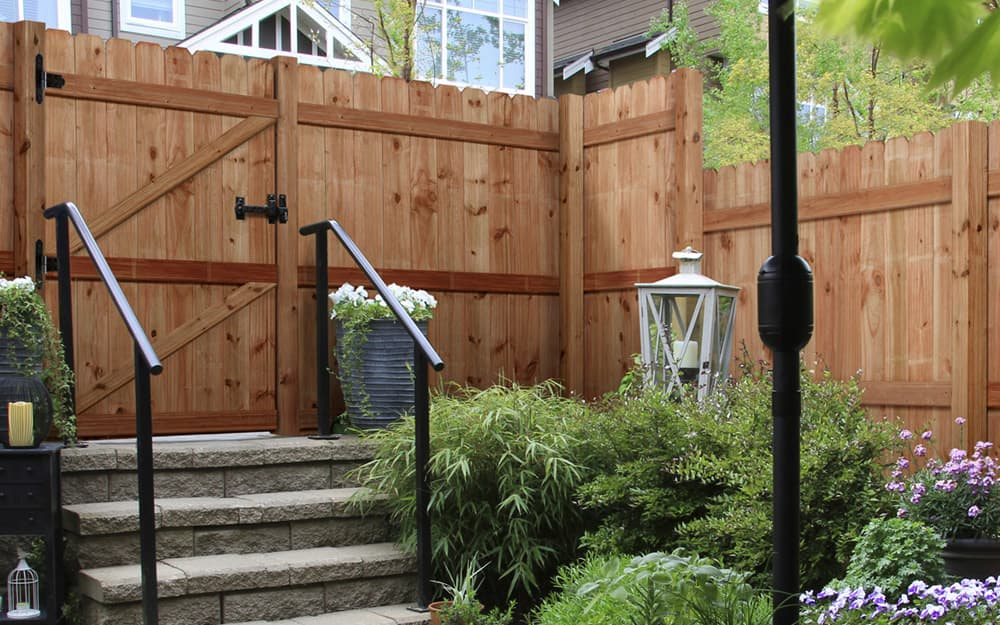 Wooden stockade-style privacy fencing with rounded tops.