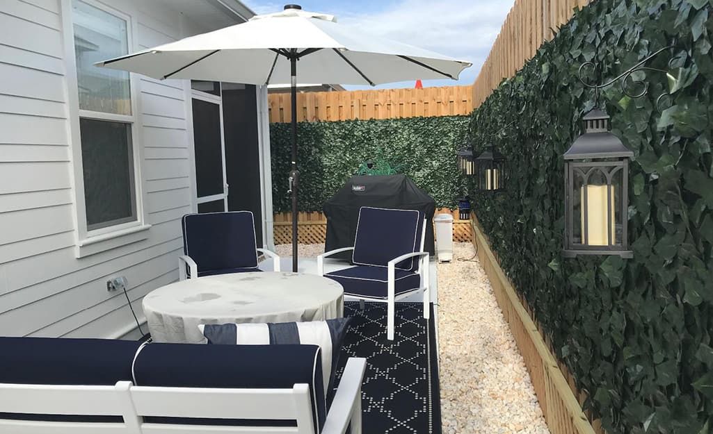 A faux ivy screen encloses a small outdoor space furnished with chairs and a table with an umbrella