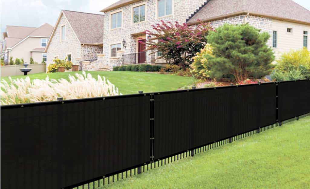 A black mesh privacy screen is attached to a black fence that divides two yards