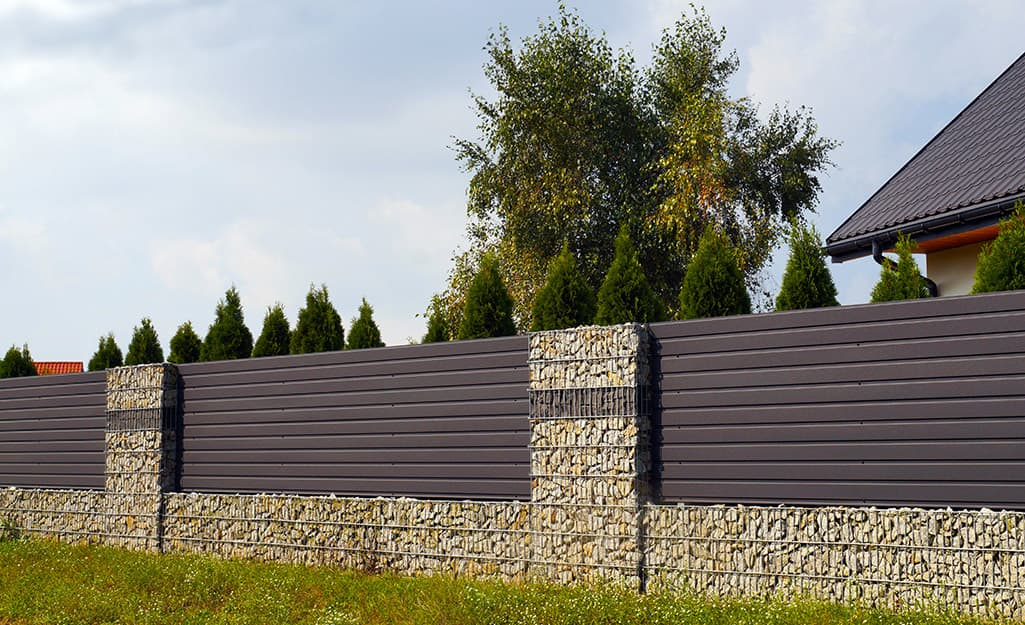 Horizontal slats and stonework give this privacy fence a modern look