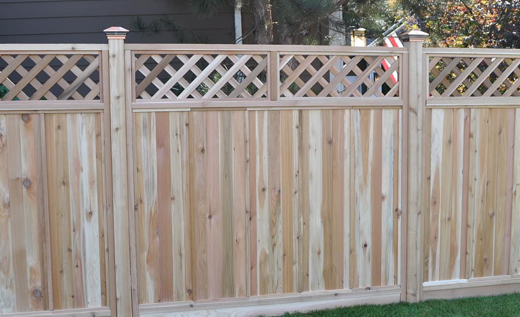 Lattice accents top a wooden fence that has decorative posts