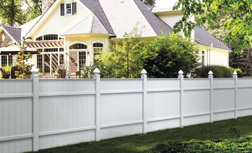 A white vinyl privacy fence marks the property line next to a light yellow house